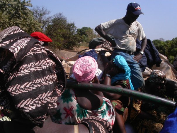 Guinea - sitting on top of second truck more passengers