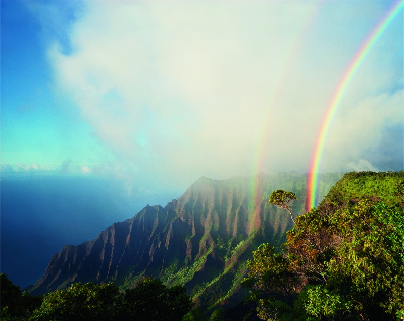 """A double rainbow arcs above the jagged cliffs and dense vegetation of Kalalau, the largest valley on Na Pali. Photo credit: Diane Cook/National Geographic """"Women of Vision"""" exhibit"""