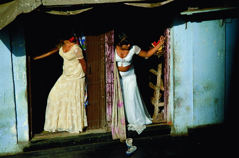 """Prostitutes, who are known as cage girls and are often sex slaves, display themselves on a Mumbai street. Photo credit: Jodi Cobb/National Geographic """"Women of Vision"""" exhibit"""