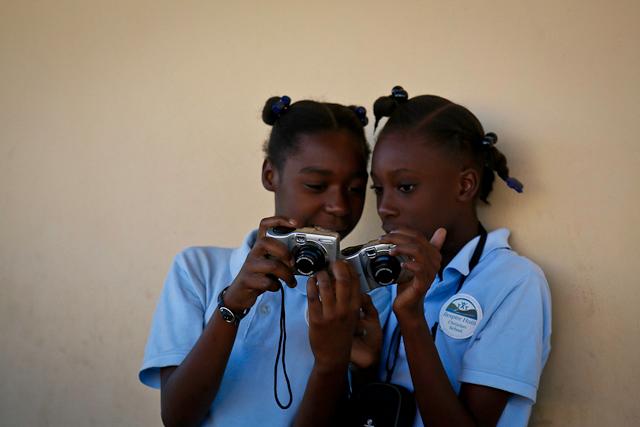 Girls looking at their first camera. Photo credit: Babita Patel