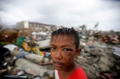 A Filipino boy stand amidst rubbles of houses in the super typhoon devastated city of Tacloban, Leyte province, Philippines. Photo credit: Save the Children