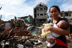 On 12 November, a woman cradling a baby stands amid debris and other destruction caused by Super Typhoon Haiyan, in Tacloban City – the area worst affected by the disaster – on the central island of Leyte. Water, sanitation and hygiene, food, medicine, shelter, debris clearance and communications are among the priority needs. Blocked roads have limited access and  the delivery of relief supplies.  On 12 November 2013 in the Philippines, Government-led emergency relief and recovery operations continue in the wake of the destruction caused by Super Typhoon Haiyan (known locally as Yolanda), which hit the central Philippines on 8 November. At least 2,500 people have been killed in the Category-5 storm; the death toll is expected to rise as more affected areas become accessible. Some 11.3 million people, including an estimated 4.7 million children, in nine regions across the country have been affected, and more than 673,000 people have been displaced. Most of them are sheltering in overcrowded evacuation centres. The storm, one of the most powerful ever recorded in the world, also destroyed homes, schools, hospitals, roads, communications and other basic infrastructure, and damaged power and water supply systems. As a result, access to the many areas remains limited, hampering humanitarian relief operations. In response to the emergency, UNICEF is rushing critical supplies to affected areas, including therapeutic food for children, health kits, and water and hygiene kits for up to 3,000 families. UNICEF is also airlifting US $1.3 million in additional relief supplies from its supply warehouse in Copenhagen for another 10,000 families, including those affected by the 7.2-magnitude earthquake that hit Bohol Province in mid-October. The shipments contain water purification tablets, soap, medical kits, tarpaulin sheets and micronutrient supplements. UNICEF is also supporting water and sanitation, education and child protection interventions for vulnerable children and famil