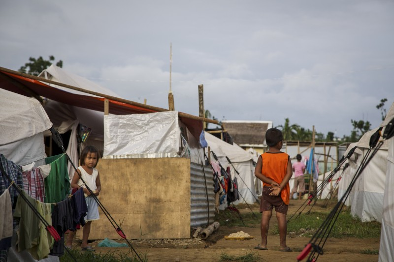 Although nearly three months have passed since typhoon Hayian hit the Philippines, millions are still without a roof over their head. Pictured here are children in en evacuation center in the town of Estancia. Due to an oil spill caused by the typhoon, some of them will never be able to turn home and will have to relocate in a different place. More and more people are managing to leave the camp and get back up on their feet and continue with their lives. Save the Children ran a Child Friendly Space in the Evacuation Center, but recently moved the space to a new location in Estancia. Photo credit: Save the Children