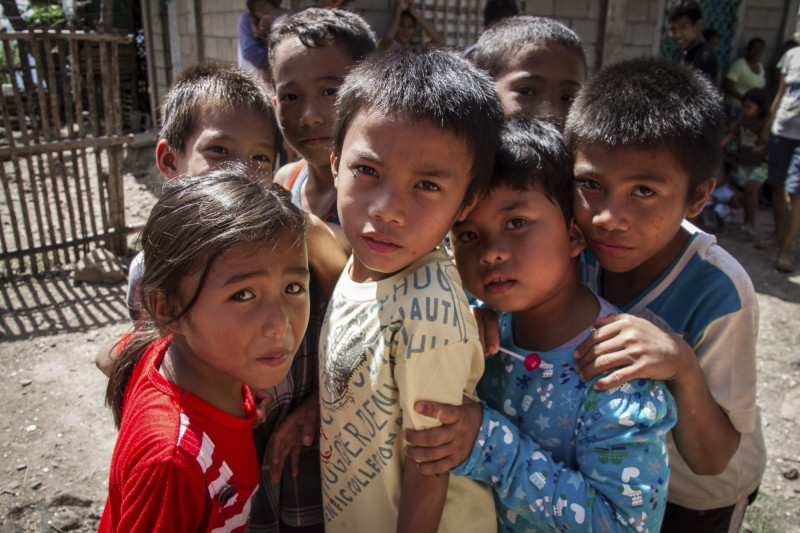 Children wait outside a mobile Child Friendly Space on the remote island of Talingting, which has been targeted as part of the Save the Children Boat programme, which visits remote islands off the coast of Panay that have been heavily affected by Typhoon Haiyan / Yolanda. Photo credit: Save the Children