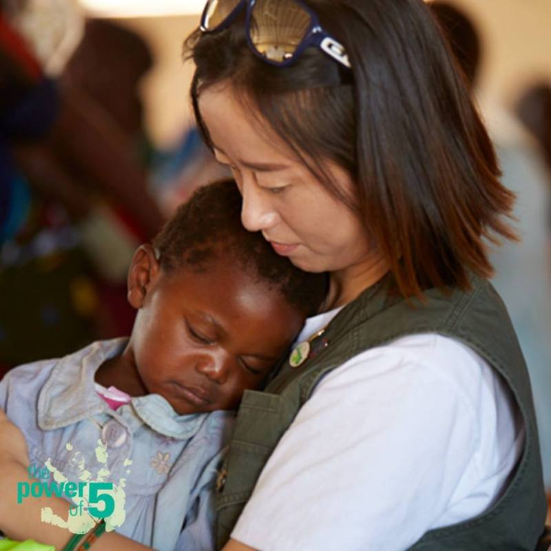 An Amway team member holding a child who is benefiting from the Power of Five products. Photo credit: Amway