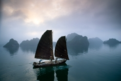An old fishing junk plies its way through the waters, Halong Bay, Vietnam, 1994.
