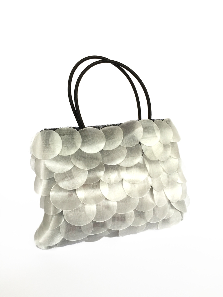 The scales of the ancient Pirarucu fish, found in the rivers and lakes of the Amazon, provided inspiration for this elegant bag. Recycled PET scales are hand seen onto mesh to create this delicate beauty.